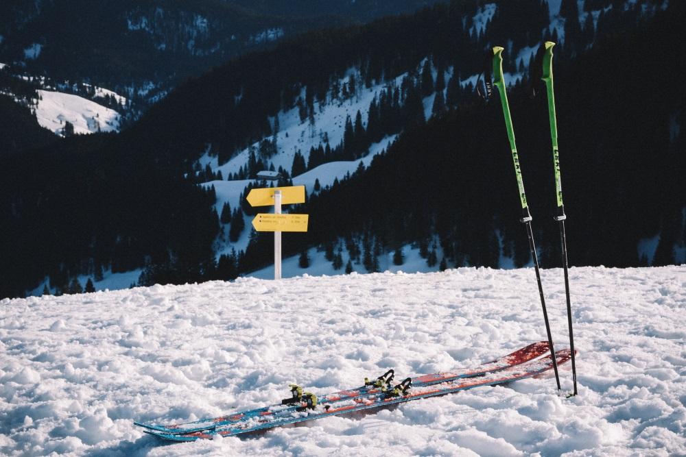 des skis au sol et des battons plantés dans la neige