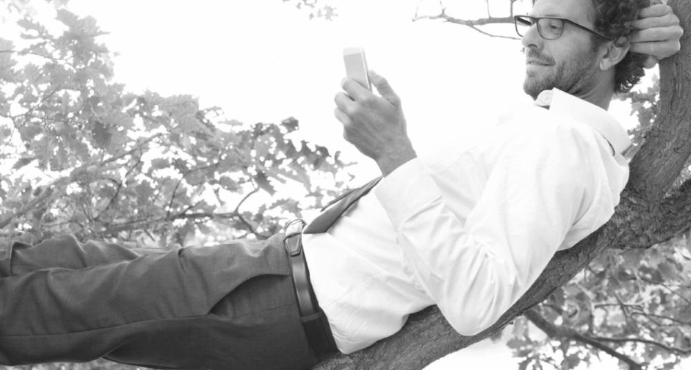 Un homme allongé sur une branche lit un livre avec des Verres progressifs Carl Zeiss
