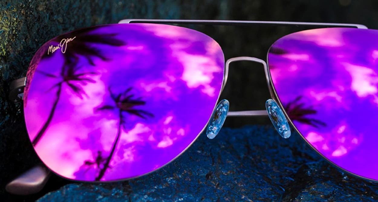 Photo de lunettes de soleil Maui Jim avec des verres roses dans lesquels se reflètent des palmiers
