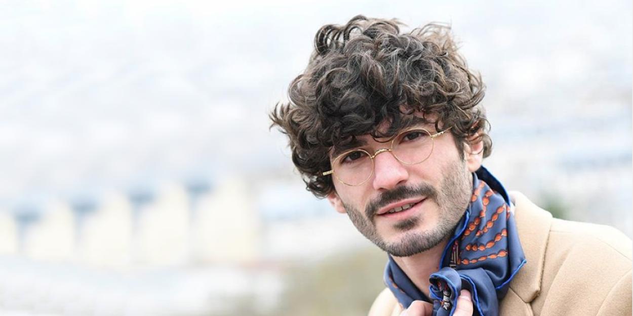 Homme brun à boucles portant les lunettes dorées rondes de la créatrice Parisienne Nathalie Blanc