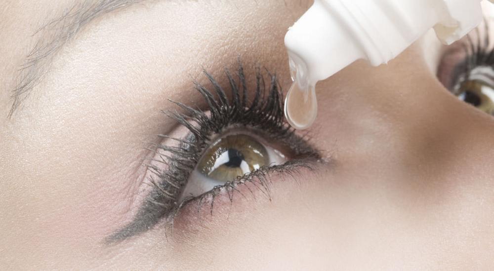 femme mettant une goutte de larmes artificielles pour soulager la sécheresse oculaire